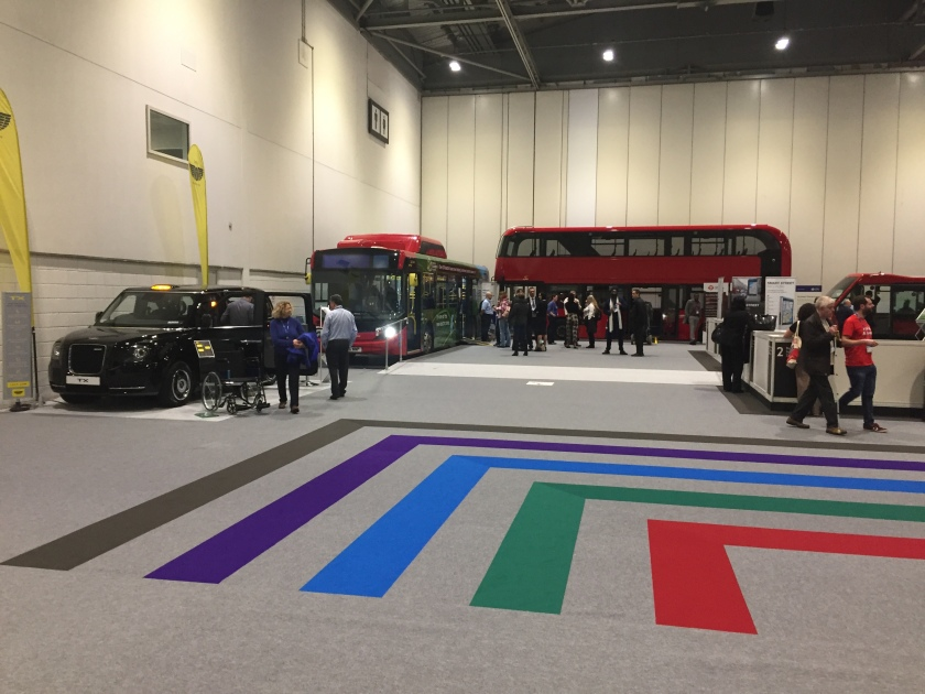 A black taxi cab, a single-decker green bus, and a double-decker red bus, on display at the Access All Areas show.