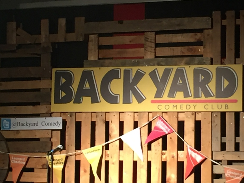 The back wall of the Backyard Comedy Club stage. A yellow banner has big black letters spelling Backyard. Under Yard is a red line, below which is smaller black text saying Comedy Club. To the left of the banner is a smaller white sign with the Twitter handle Backyard_Comedy, with an underscore between the 2 words. Stretched along the length of the wall are a row of yellow and red triangular flags, each with the words Leonard Cheshire on them.