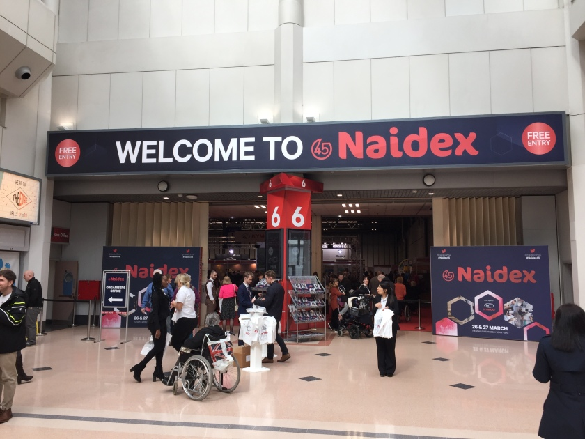 The large entrance to the Naidex show in the Birmingham N.E.C. A large banner with a dark background across the top fo the entrance says Welcome To Naidex, with the first 2 works in large white letters followed by the word Naidex in red. Red circles at each end of the banner contain white text saying Free Entry.