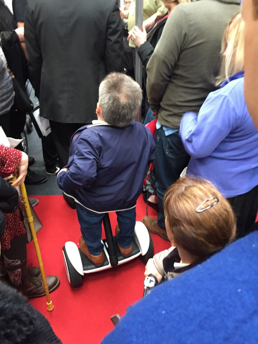 Warwick Davis standing on a small Segway machine, which is taking him through a large crowd of people.