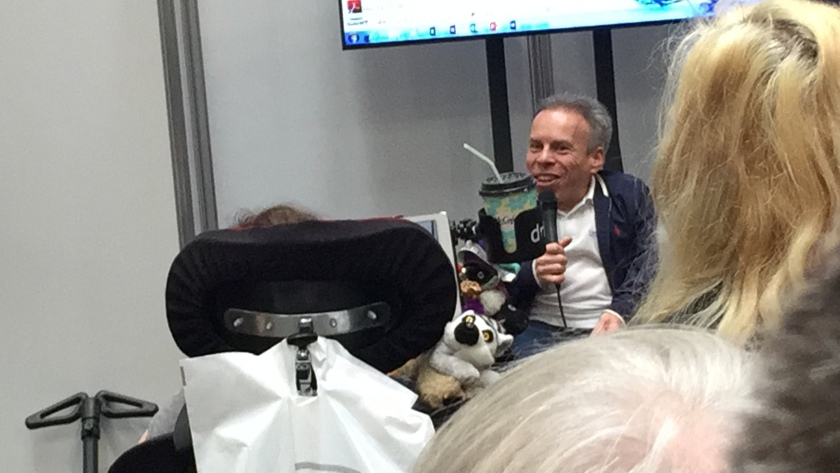 Warwick Davis sitting on a table and holding a microphone as he addresses the audience.