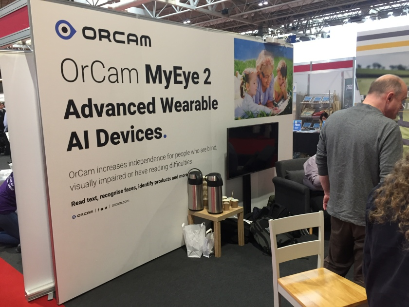 The OrCam stand at Naidex. Text on the large white backboard reads OrCam My Eye 2, Advanced Wearable AI Devices. OrCam  increases independence for people who are blind, visually impaired or have reading difficulties. Read text, recognise faces, identify products, and more. OrCam.com