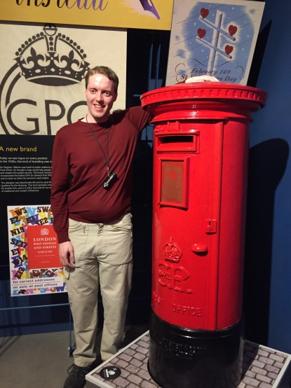 Glen smiling as he poses next to a red post box, resting his left arm on top of it. He's wearing a red top and light coloured cargo trousers, and has his monocular around his neck.