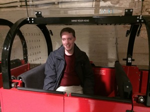 Glen smiling as he sits in one of the small carriages of the red Mail Rain train.