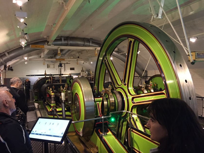Machinery in the engine room under Tower Bridge, driven by a very large green wheel.