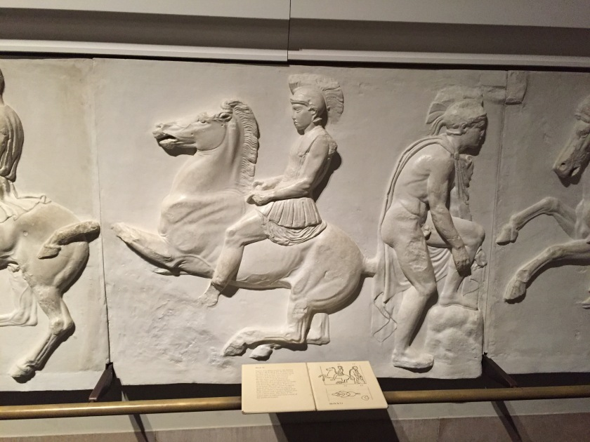 Large tactile casts on the wall in the Parthenon Gallery, including a soldier sitting on a horse that appears to be in motion with its front legs up, and a man to the right with his foot up on a rock as he adjusts his footwear.