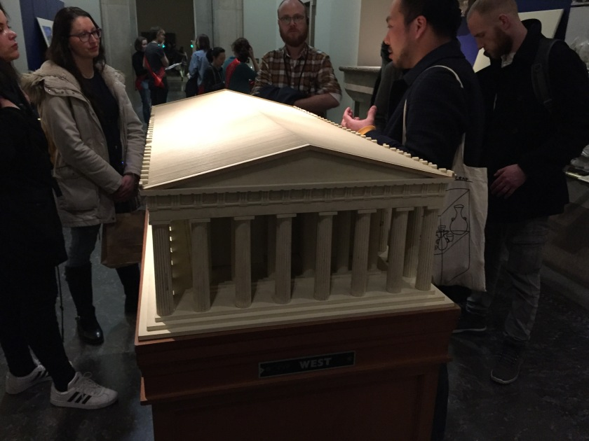 Model of the Parthenon building viewed from one end, with the triangular roof that slopes down on each side, and 8 pillars across the front of the structure.