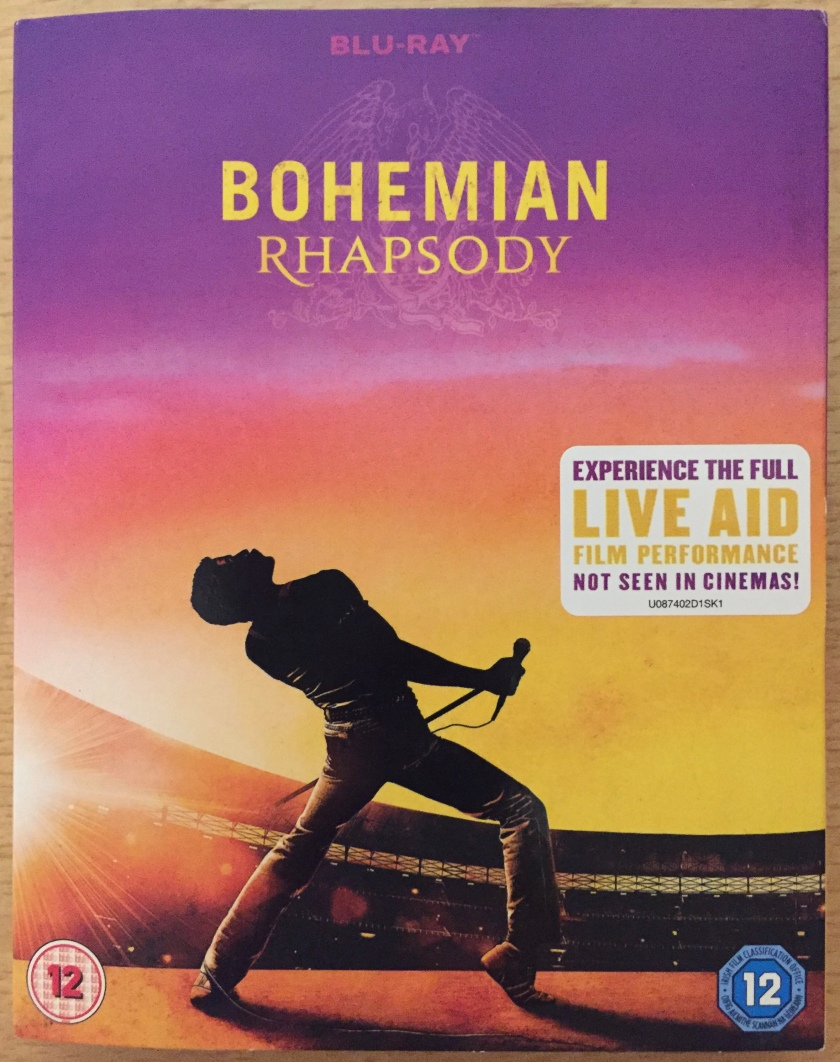 Blu-ray cover for the Bohemian Rhapsody movie. The image shows Freddie leaning back and holding the microphone stand across his front, while on stage during Live Aid in Wembley Stadium, under a multicoloured sky that ranges from purple to orange to yellow. A white sticker has text saying Experience the full Live Aid film performance not seen in cinemas.