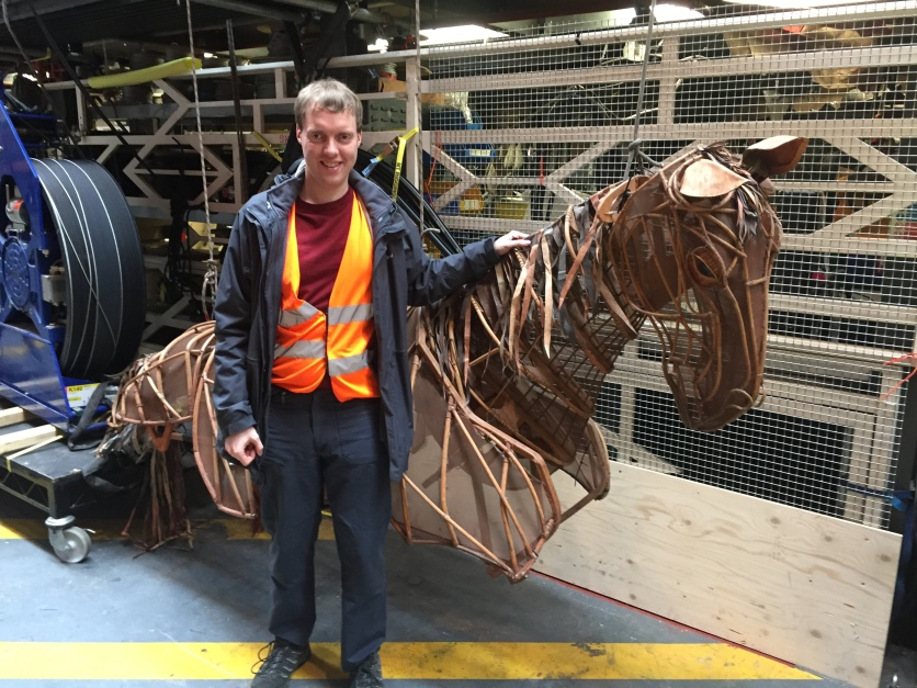 Glen standing with a large wooden frame horse model used in War Horse.