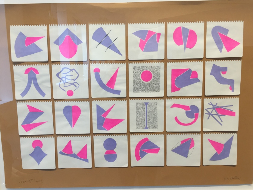 A grid of 24 artworks on a board, 6 across and 4 down. Each drawing is on a small square piece of paper, with square, turret-like edging at the top that shows it was removed from a notebook. The drawings use a mixture of pink and purple shapes, usually one of each connected in some way, but there are other variations too.
