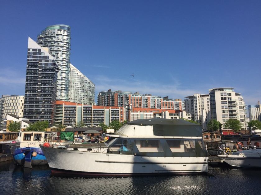 Boats parked in Poplar Dock Marina, with blocks of flats of varying heights and designs in the background, including a couple with diagonal sloping roofs, all under a clear blue sky.