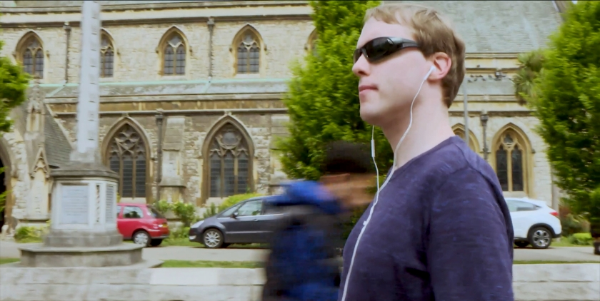 Wearing sunglasses and white Apple earphones, Glen looks around him as he walks past a large church.