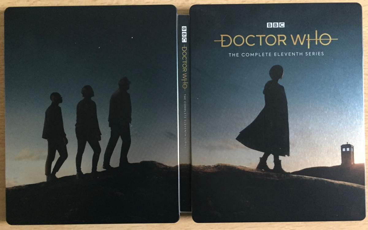Steelbook cover for Doctor Who Series 11 on Blu-ray, unfolded to reveal the full image. The 3 companions and the female Doctor are silhouetted on a hill beneath a clear dark sky, looking towards the Tardis sitting on another hill in the distance on the far right.