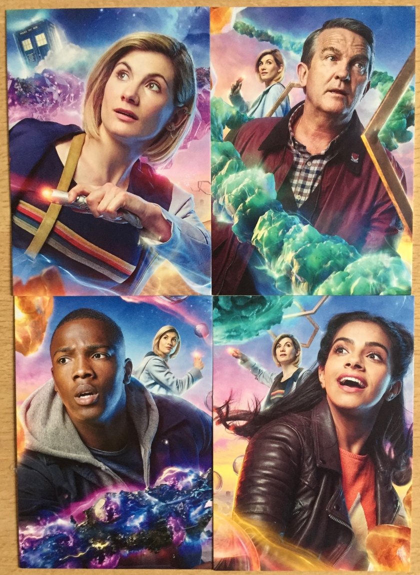 4 postcards, each with a colourful portrait of a different member of the Tardis team, namely the Doctor, Graham, Ryan and Yasmin. In the portraits of the 3 companions, the Doctor is standing behind them. In all images, the Doctor is holding out her lit-up sonic screwdriver.