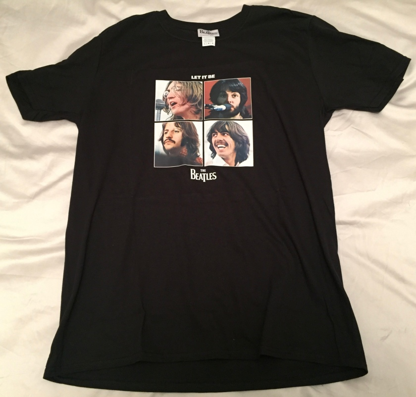 Black T-shirt featuring a grid of 4 photos of the members of The Beatles. Above the photos in white text is the wording Let It Be, while below the photos is the band's logo.