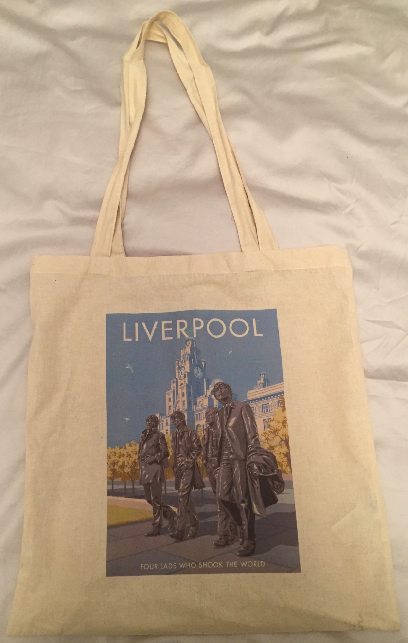 Large white cloth bag, with artwork showing statues of all 4 members of the Beatles in front of the Royal Liver Building, whose spire with a clock on each side it can be seen in the background. White text below the statues says Four Lads Who Shook The World.