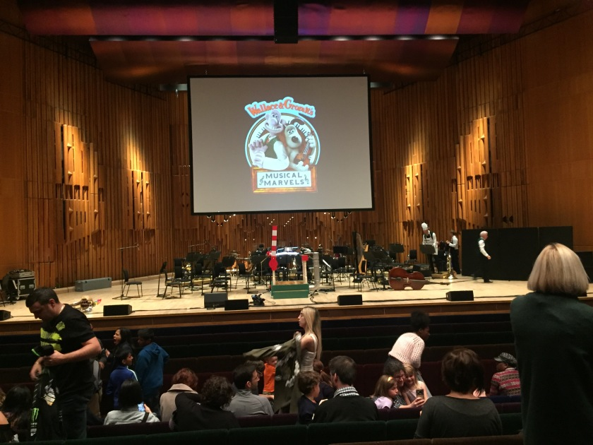 The stage for Wallace & Gromit's Musical Marvels, after the orchestra have left. Wallace & Gromit appear on the large screen at the back, in among the text giving the title of the show. The conductor's podium has a red and white striped lever, rather like a railway signal, that can be lowered behind the conductor.
