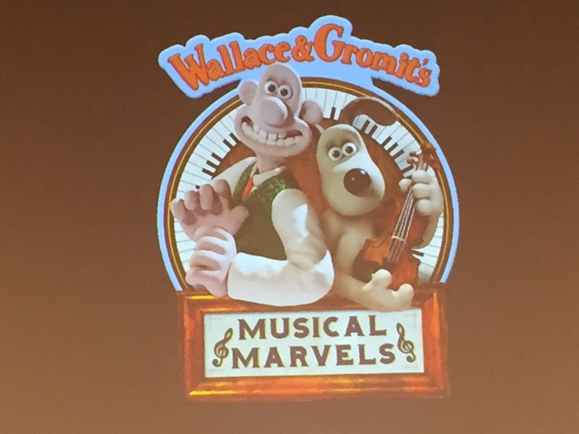 The characters of Wallace & Gromit standing next to each other. Wallace is smiling widely, while Gromit holding a violin. They are standing in front of a circle made of piano keys. Text reads Wallace & Gromit's Musical Marvels, with the character names above the circle, and the show title at the bottom.