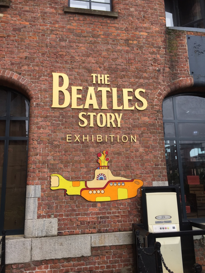Sign for The Beatles Story Exhibition, written in gold letters on the brick wall of the museum. Below the lettering is a cartoon image of a yellow submarine.
