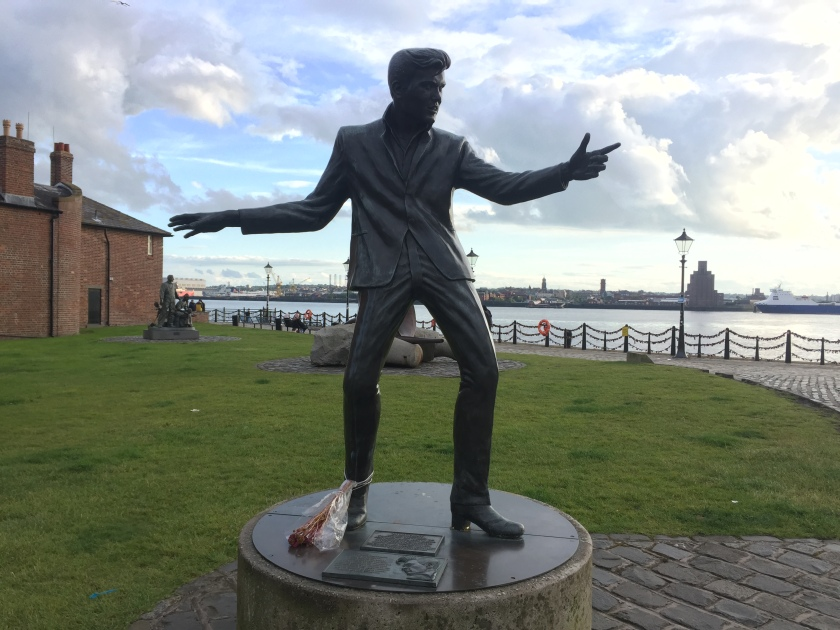 Life-size statue of Billy Fury, standing legs apart with one arm stretched out and pointing in front of him, and the other arm stretched out behind, as if he's in the middle of a dance move. The River Mersey is in the background.