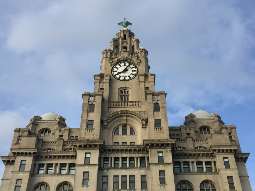 The spire of the Royal Liver Building, with a black and white clock face on the front, and a statue of a bird with outstretched wings standing on the very top of the spire.