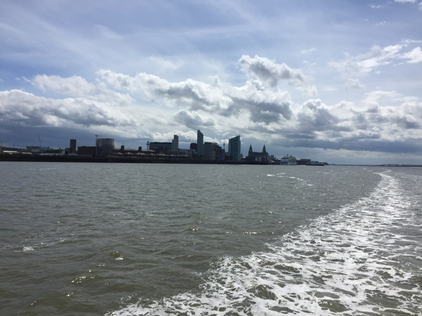 View from the Mersey Ferry towards Liverpool. The front and rear spires of the Royal Liver Building can be seen in the distance, along with a large cruise shop moored near it. A curved trail of frothing water, left behind by the cruise during its journey, is also visible.