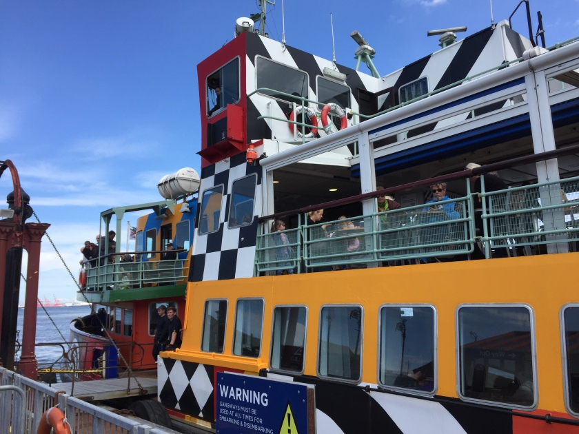 The colourful Dazzle Ferry boat, with bold, striking patterns in yellow and blue, along with large checkerboard patterning and wide diagonal stripes in black and white.