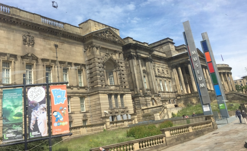The large World Museum building in Liverpool, the entrance of which is under a high canopy held up by tall pillars. Posters outside the museum advertise the Astronomy Photographer Of The Year, The Planetarium and Big Art For Little Artists.