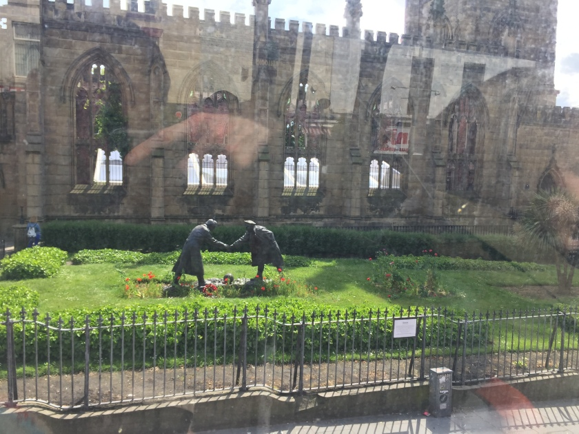 The Christmas Truce statue on a patch of grass outside the Bombed Out Church in Liverpool. The statue, called All Together Now, shows 2 soldiers facing each other as they shake hands, with a football on the ground between them.