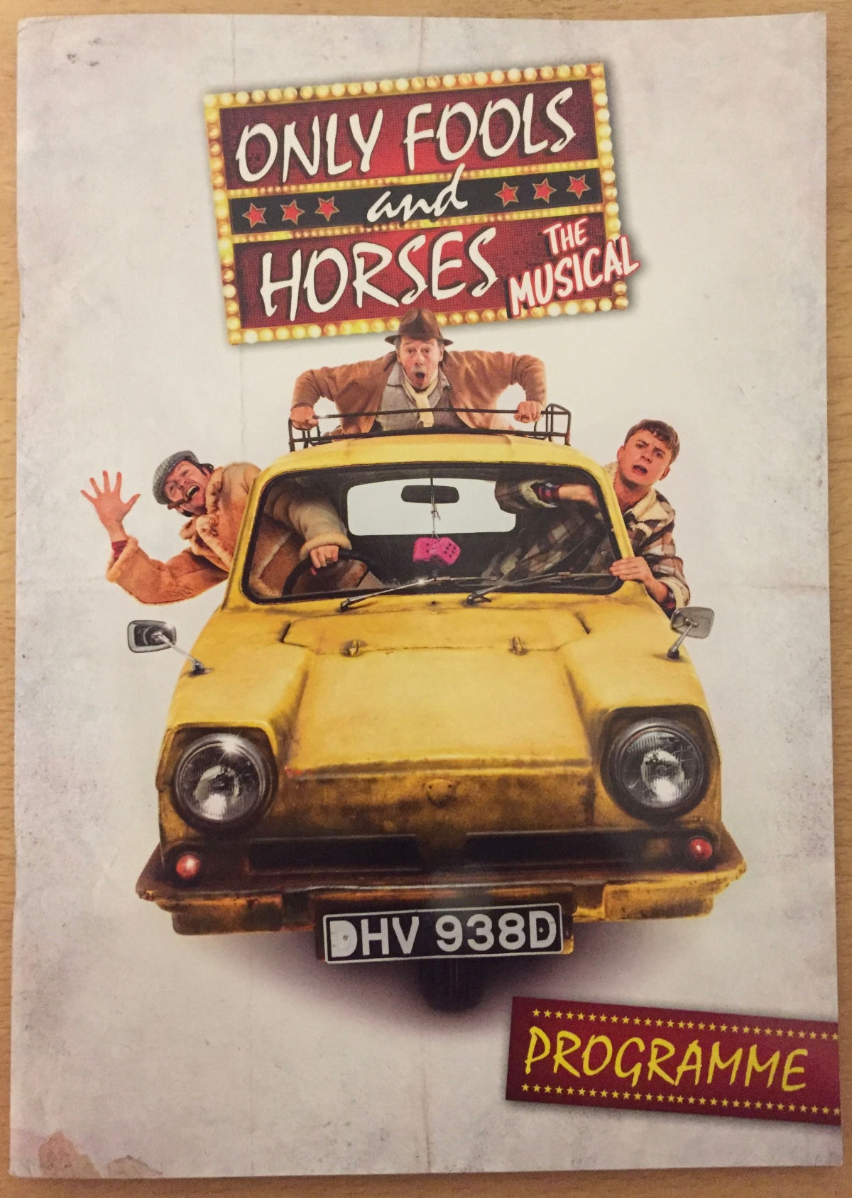 Cover of the programme for Only Fools And Horses, The Musical. Below the show logo is a large image of the yellow three-wheeled Reliant Regal van facing us, with 2 pink fluffy dice hanging from the rear view mirror in the centre. Del Boy and Rodney are leaning out of their side windows, with Del Boy waving and smiling with a cigar in his mouth, while Grandad is on the roof rack holding on tightly.