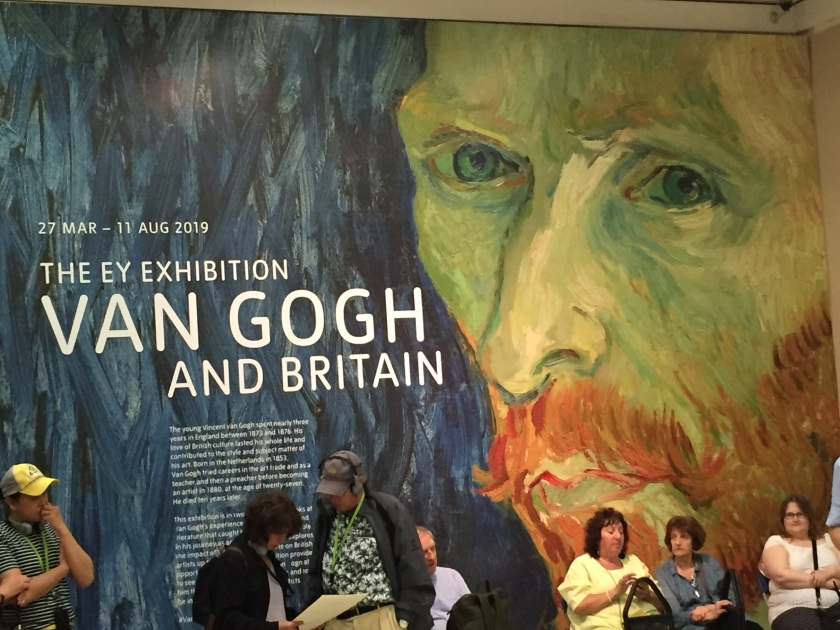 A large portrait of Vincent Van Gogh's face on a wall in Tate Britain. Text next to it says 27 March to 11 August 2019, The E.Y. Exhibition, Van Gogh And Britain. Below that is a description of the exhibition in smaller text