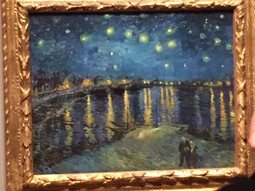 Van Gogh painting of a wide river stretching into the distance, with lights from buildings along each riverbank, and stars shining down from the sky. At the bottom of the painting, 2 people stand together on a patch of land overlooking the river.