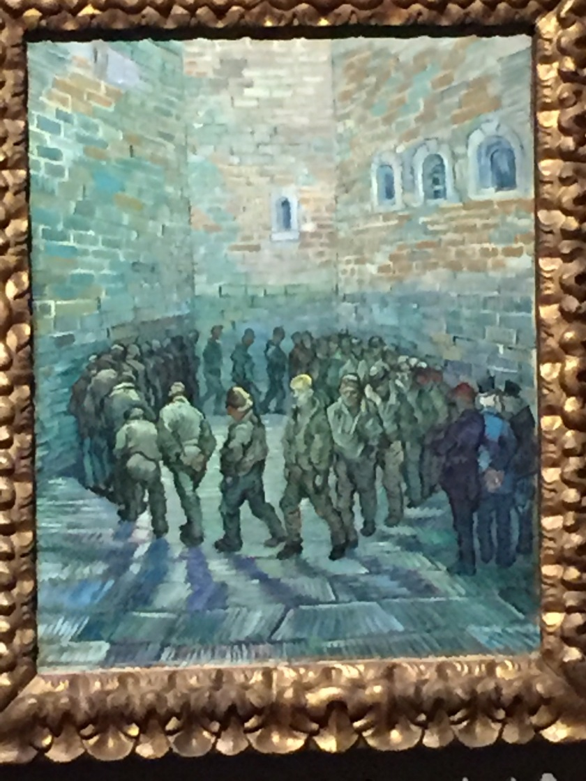Van Gogh painting showing a group of men in plain grey uniforms, trudging around in a circle in a small courtyard, with high brick walls all around them, as 3 people watch from the bottom-right corner.
