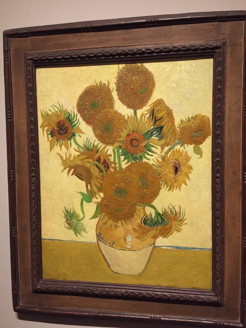 Sunflowers painting by Vincent Van Gogh, showing a small vase holding a big bunch of sunflowers, some of which are in bud, some of which are fully open, and some of which appear to have died.