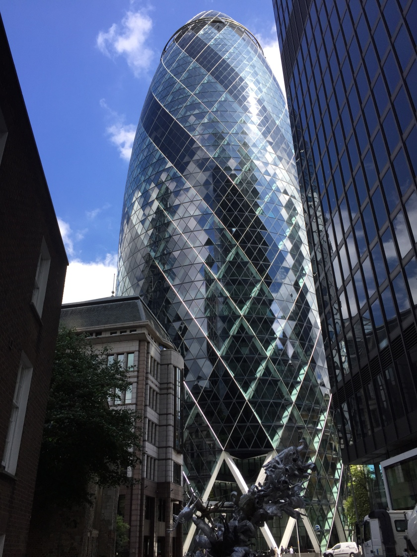 The very tall Gherkin building, which is named after its shape. Many small windows make up the exterior, arranged in white-edged diamond shaped formations that spiral steeply around the building. Every third spiral of windows is a darker colour to the rest.