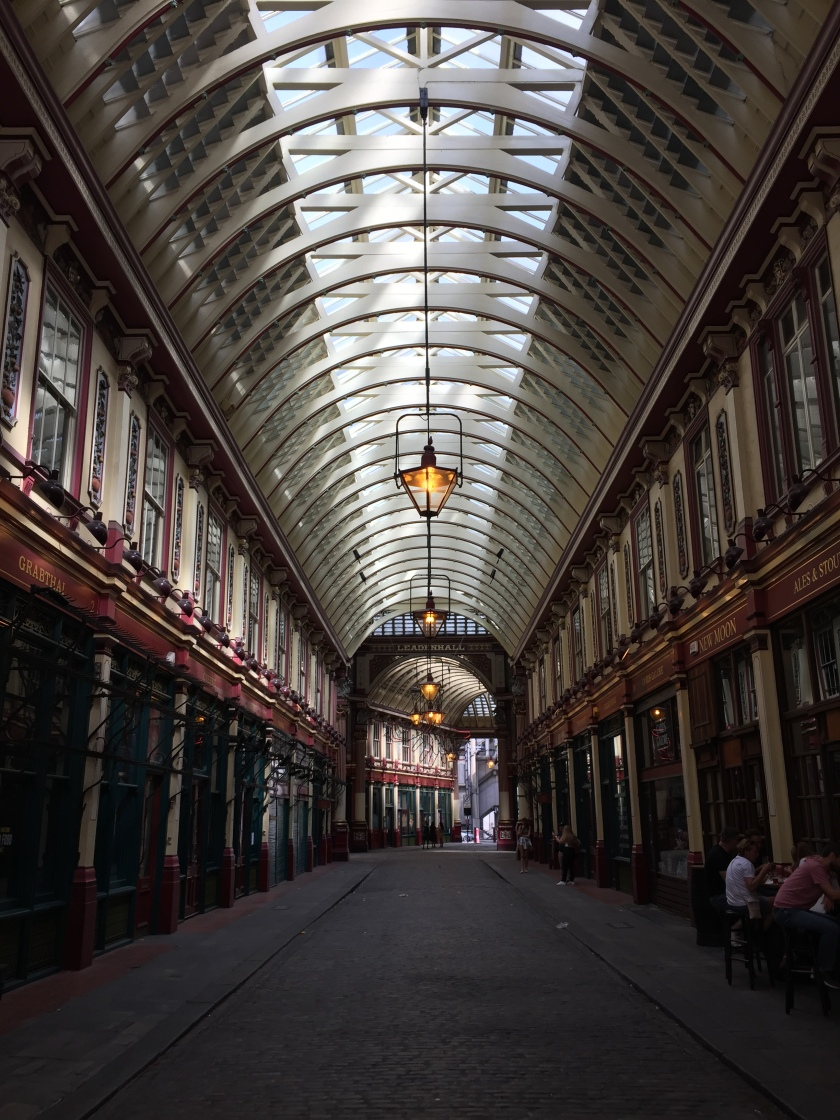 Interior of the historic Leadenhall Market, with many shops and restaurants lining each side of the street. The street is covered by a curved roof, with windows all along its central length that allow daylight in.