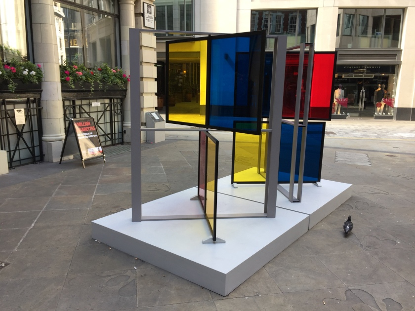 Sculpture made of 8 large square panes of glass, each a different colour, being either yellow, red or blue. They are arranged in 2 large metal grids, which stand diagonally on 2 adjacent white squares, using opposite diagonals. In each grid the top and bottom pair of panes each swivel in the centre, and have been turned to face in different directions.