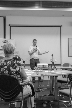 A black and white photo of Glen standing and talking into a microphone. He is wearing a white t-shirt with the Aniridia Network logo on it, while next to him is a tall free-standing banner for Aniridia Network UK, and a laptop on a podium with an Aniridia Network Conference 2019 sign on its open lid.
