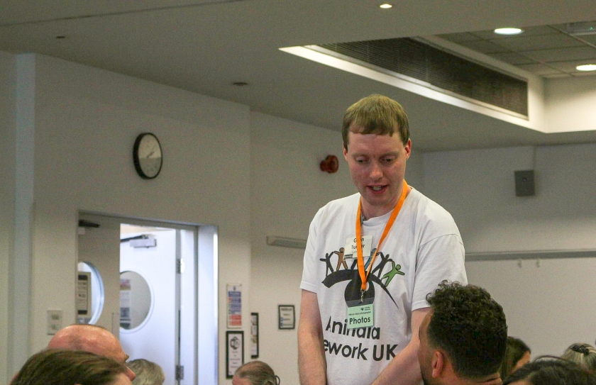 Glen talking to other delegates at the Aniridia Network Conference. He is wearing a white t-shirt with the Aniridia Network logo on, which features a line of differently coloured gingerbread-men-type figures standing on the eyebrow of an eye, with a black pupil beneath. Around his neck, Glen also has an orange lanyard, on the bottom of which is a plastic sleeve with a card saying Photos, designating him as an official photographer for the event.