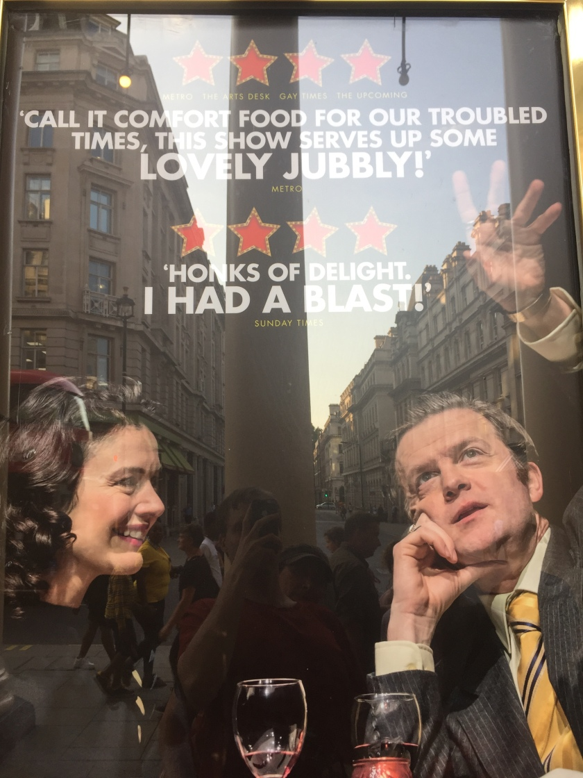 Poster for the Only Fools And Horses musical, showing Raquel and Del Boy sharing drinks on a date. Above them are a couple of review quotes. Metro says Call it comfort food for our troubled times, this show serves up some lovely jubbly! The Sunday times says Honks of delight, I had a blast!