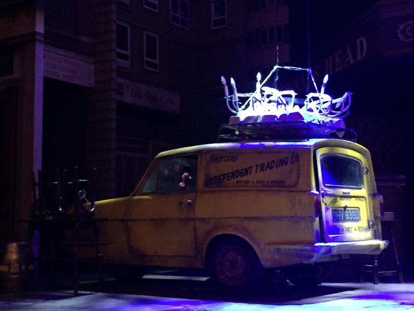 The yellow three-wheeled Reliant Regal van used by the Trotter family, parked on stage at the Only Fools And Horses musical.The words Trotters Independent Traders, New York,  Paris, Peckham are written in black on the side, while a smashed chandelier sits on the roof.