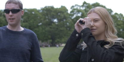 In a park, blonde female student Amy looks through Glen's monocular while he stands beside her.