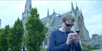 Standing in front of a large church, Glen is wearing earphones and sunglasses while looking at his phone.