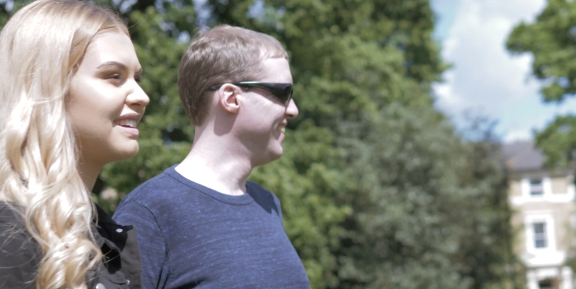 Amy and Glen standing and smiling together in the park in the sunshine.