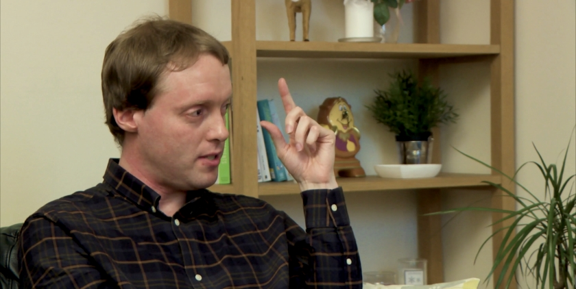 Close-up of Glen gesturing with his fingers near his eye, during his interview in a living room.