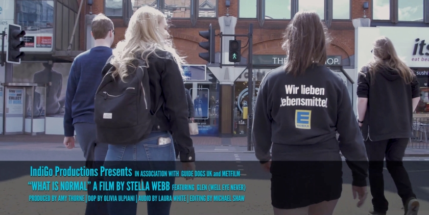 Credits screenshot from the documentary, showing Glen, Amy and Laura crossing a pedestrian crossing. Text at bottom of the screen credits Glen, the various members of the production team, and the associated organisations Guide Dogs UK and Met Film.