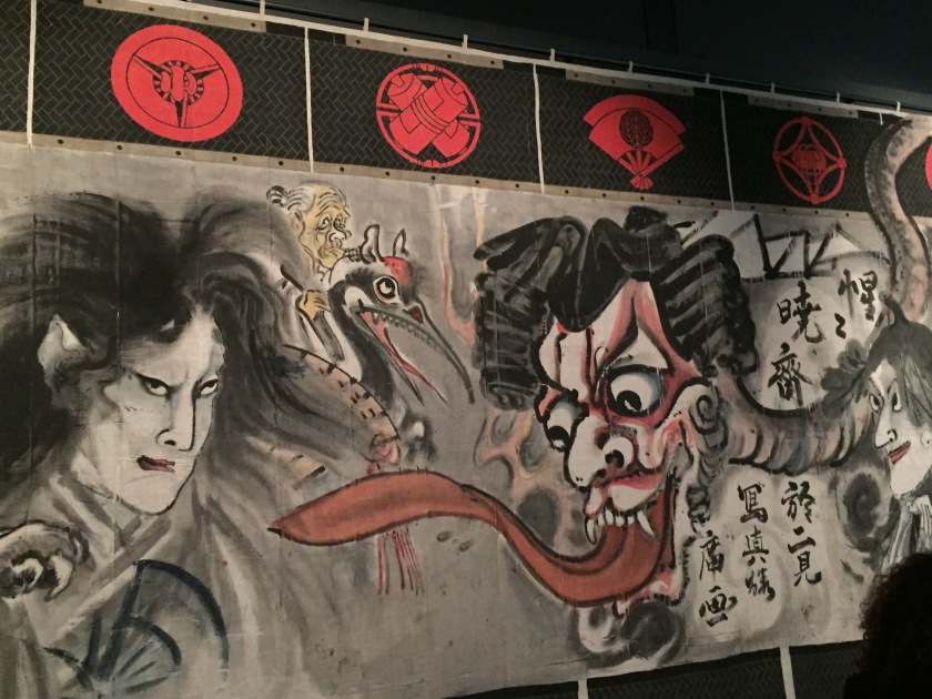 Section from a large manga wall mural. On the right is a large head with a long red tongue snaking out of its mouth towards a man on the left side. In the centre at the back is a large bird with teeth along the inside of its beak, with an elderly character riding on its back.