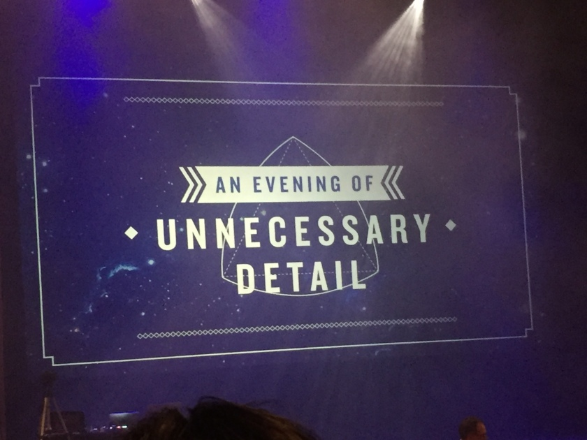 The title frame for An Evening Of Unnecessary Detail, filling the screen at the back of the stage below colourful lights.