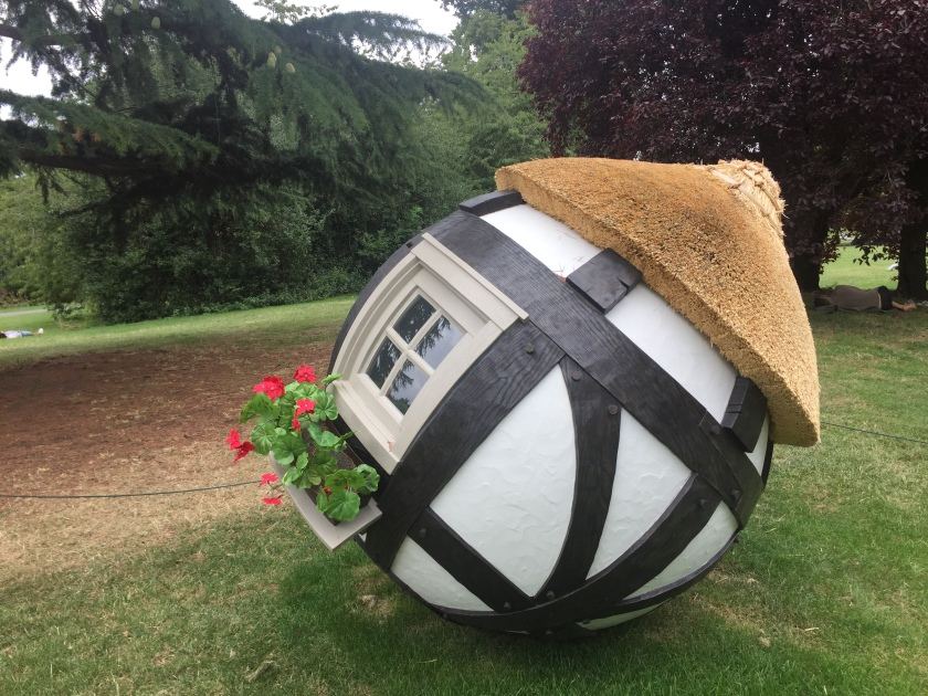 Sculpture of a small house in the shape of a sphere, with a pointed thatched roof, white walls with thick black stripes going across and down around it, and a window with a small window box containing red roses.