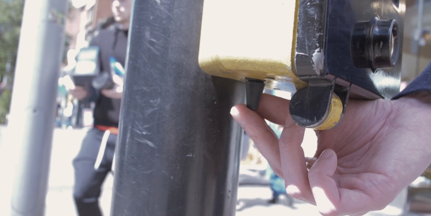 Close-up of Glen's fingers feeling the black rotating cone attached to the underside of a wait sign at a pedestrian crossing.
